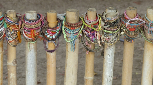 Colorful bracelets on posts marking mass graves at Killing Fields, Cambodia