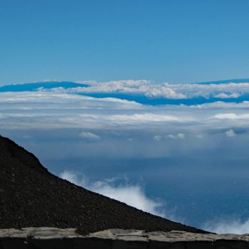 Clouds hover over Hawaii in the distance, looking out from Maui's summit