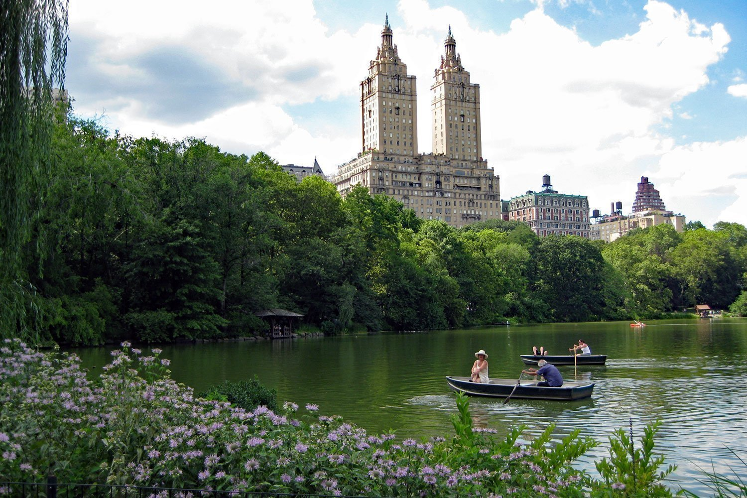 Rowers on Central Park pond with iconic Upper West Side buildings in the background