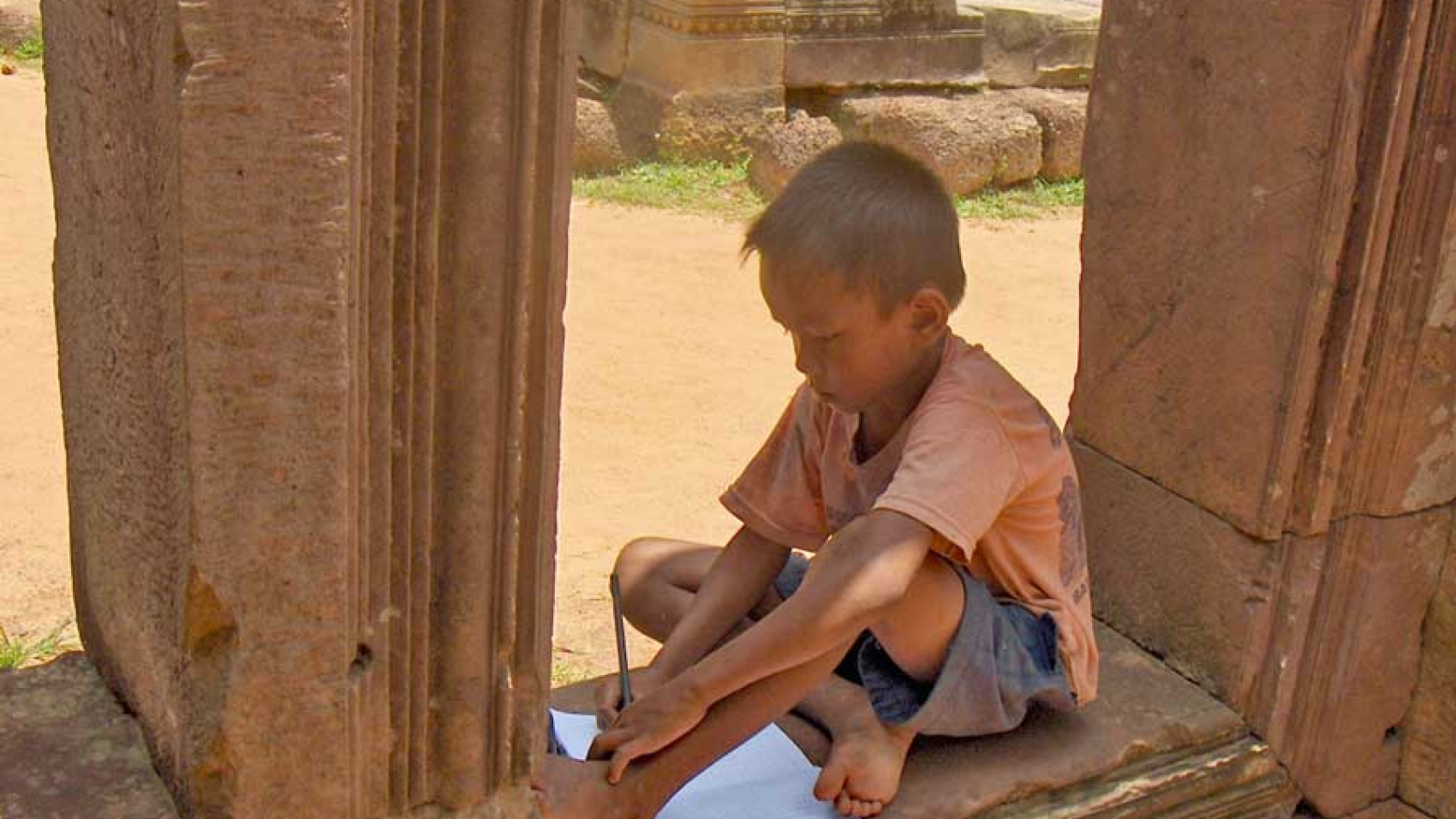 Young boy drawing in temple ruins near Siem Reap