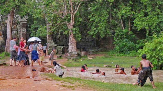 Kids jump into a massive puddle as it rains at Ta Prohm Temple, Siem Reap