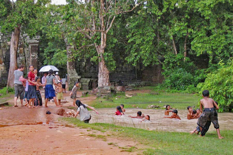 Kids jump into a massive puddle as it rains at Ta Prohm Temple, Siem Reap