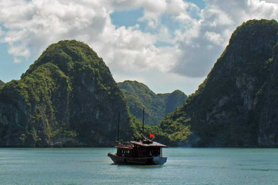 Single boat floating under beautiful skies in Ha Long Bay, Vietnam
