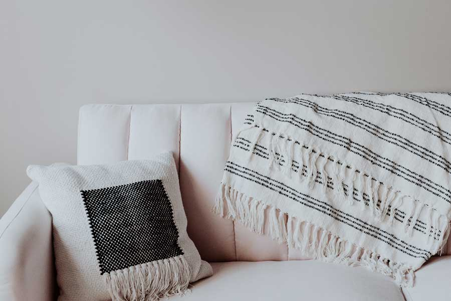 Tidy and welcoming couch with pillow and blanket