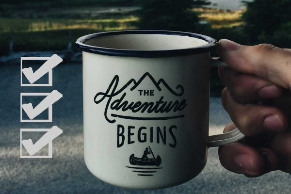 """A checklist and """"The adventure begins"""" mug in front of a beckoning road, trees and lake"""