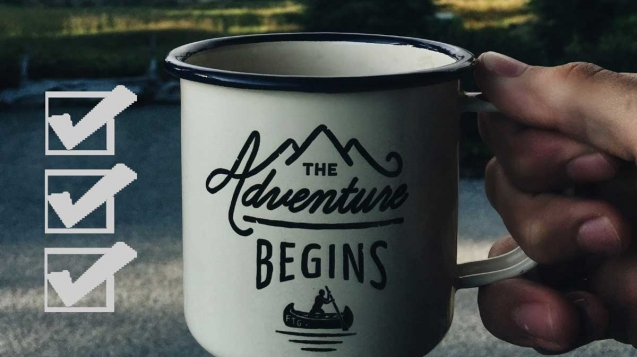 "A checklist and ""The adventure begins"" mug in front of a beckoning road, trees and lake"