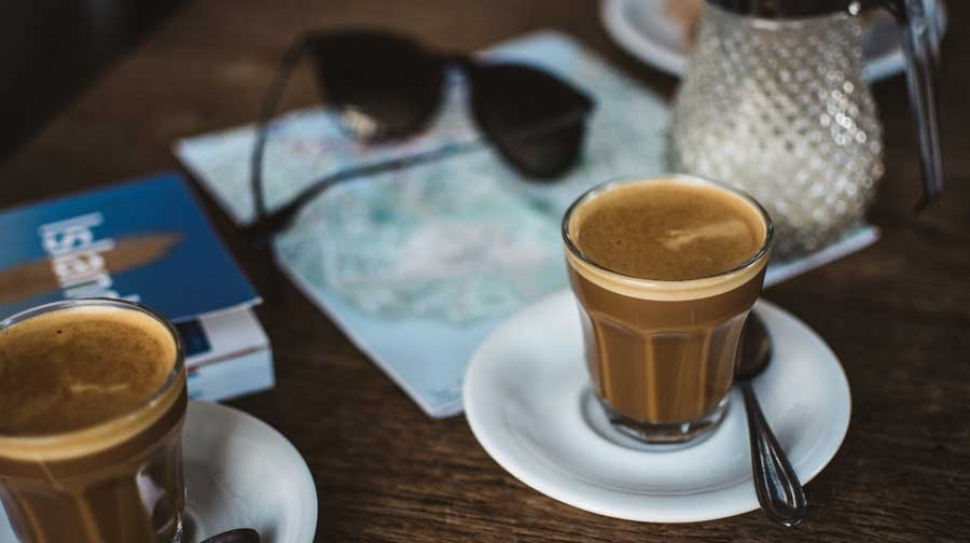 Browsing travel guides and maps over delicious coffee