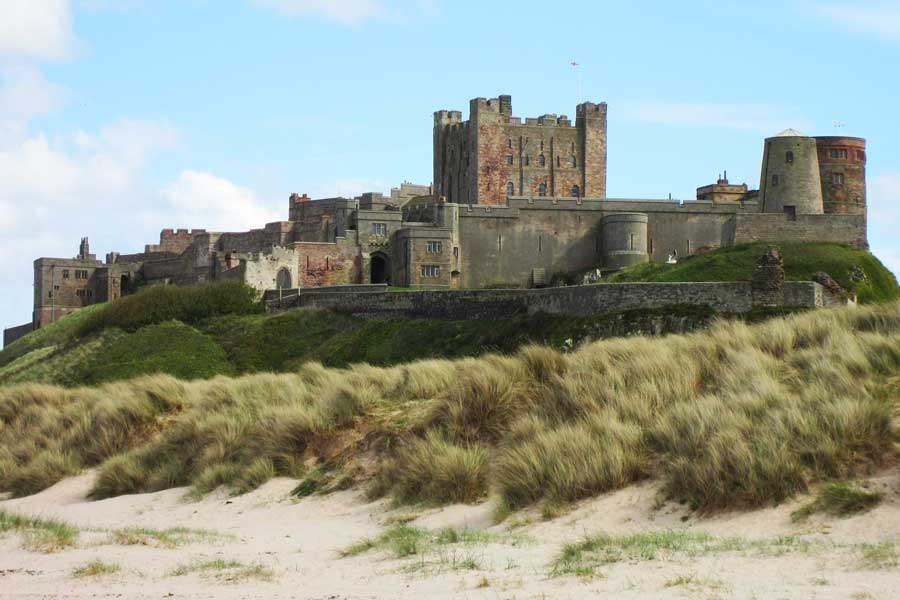 Mighty Bamburgh Castle rises from the sandy beach, England