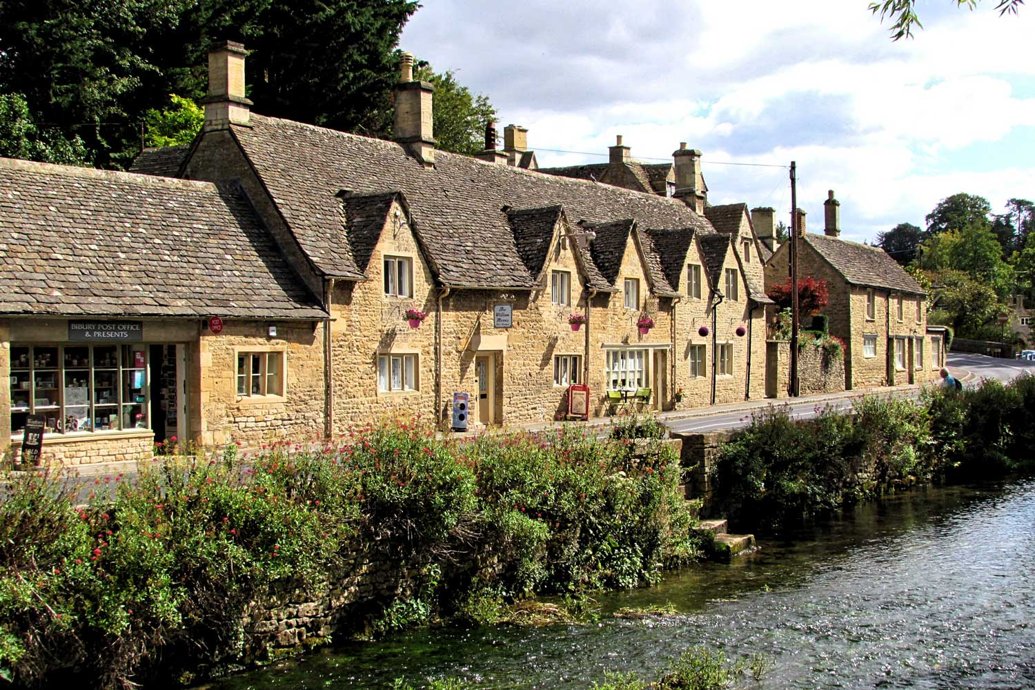 Picturesque thatched houses along the river in the Cotswolds, England