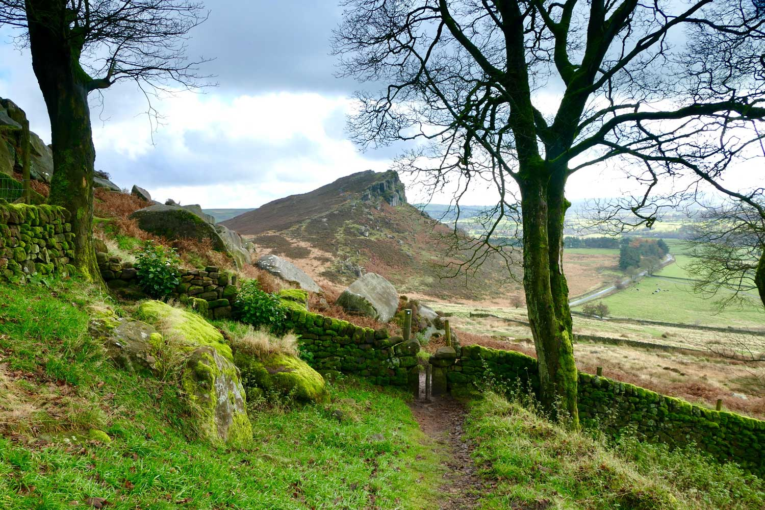 Worn narrow path through gates and over grassy fields of Peak District, England