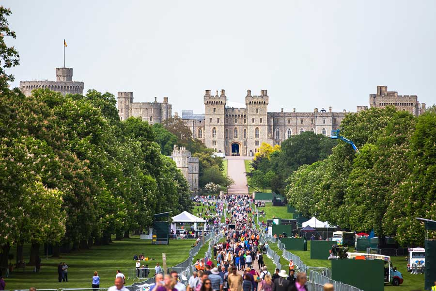 Crowds of visitors on path before the mighty Windsor Palace in England