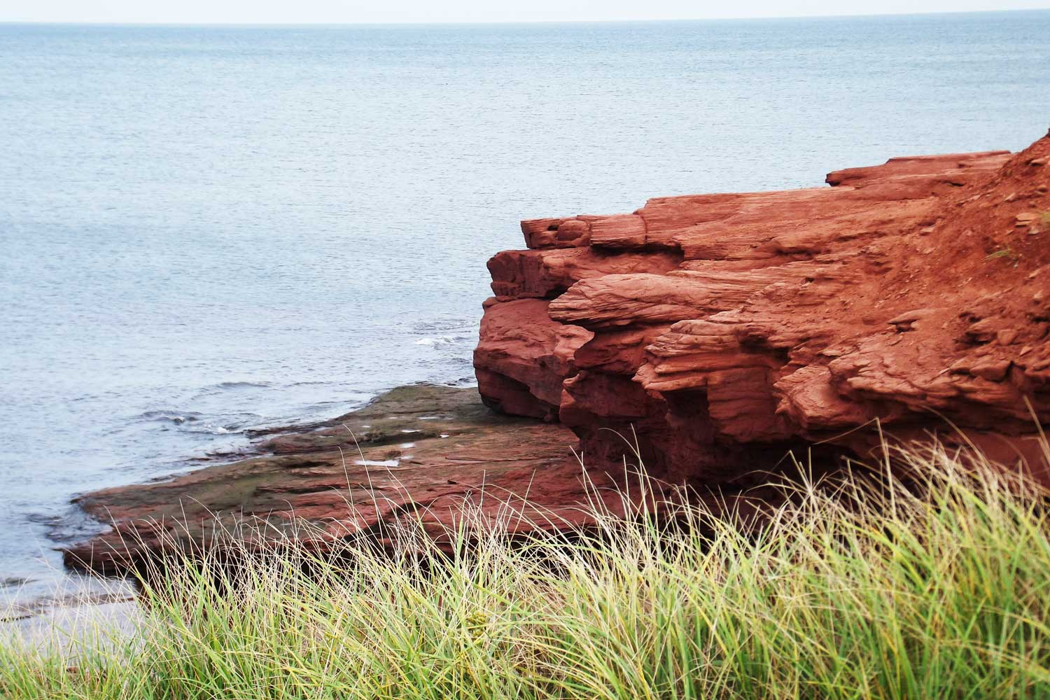 Brilliant red cliffs contrast vivid greenery and blue sky of PEI