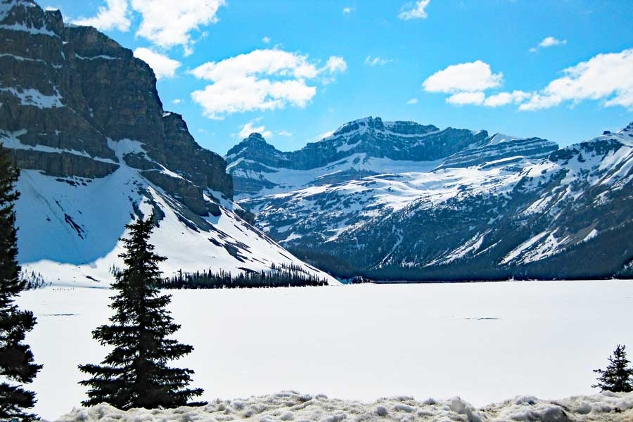 Snow-covered lake under the towering mountain summits and beautiful blue sky