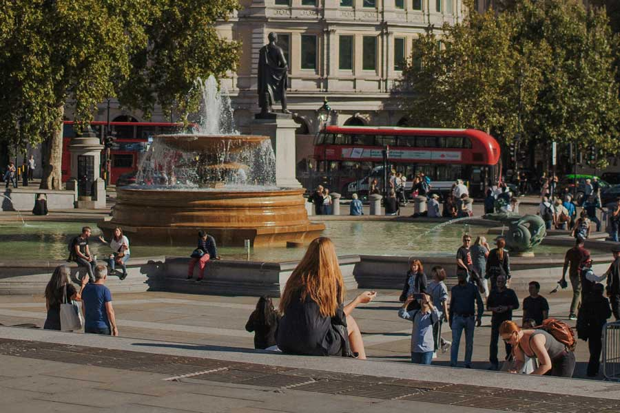 Relaxing day by a fountain as London tour bus passes by
