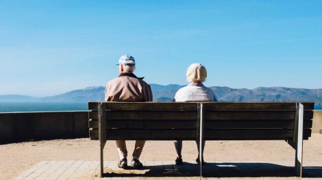 Aging couple on bench overlooking mountains
