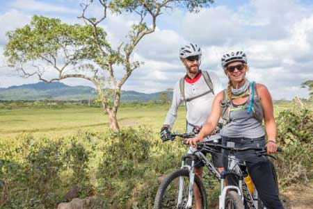 Couple cycling in Tanzania, Christmas vacation ideas for couples, Intrepid Travel
