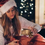 Woman wrapping a gift under the glow of Christmas tree lights