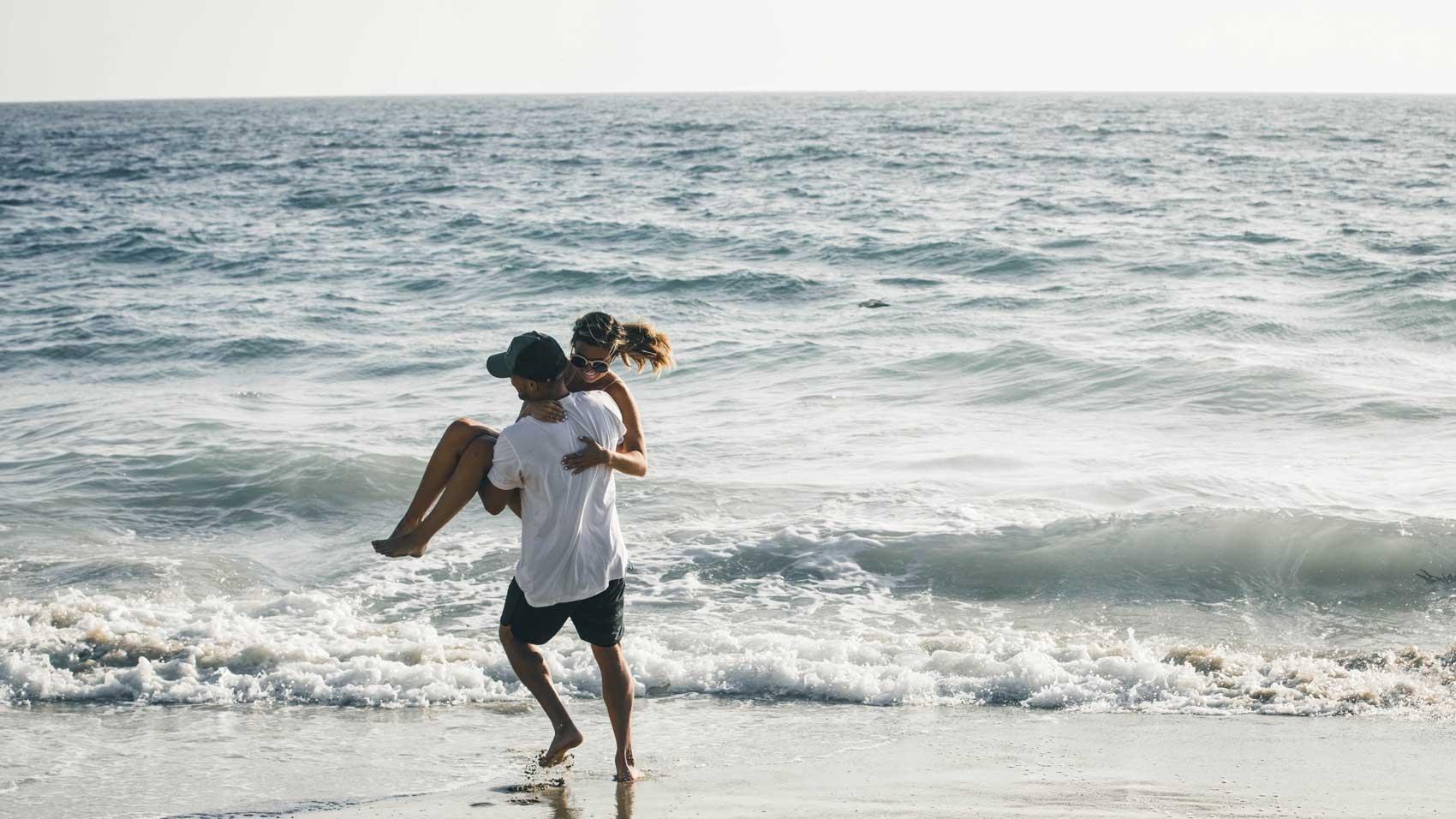 Couple having fun in ocean waves, Romantic getaways USA