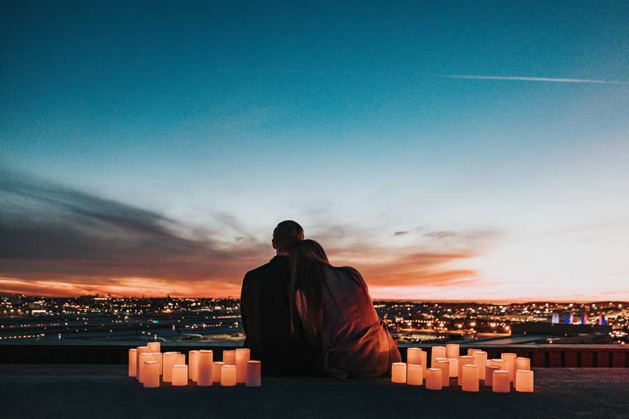 How to plan a romantic getaway, couple at dusk overlooking city, how to make a trip romantic